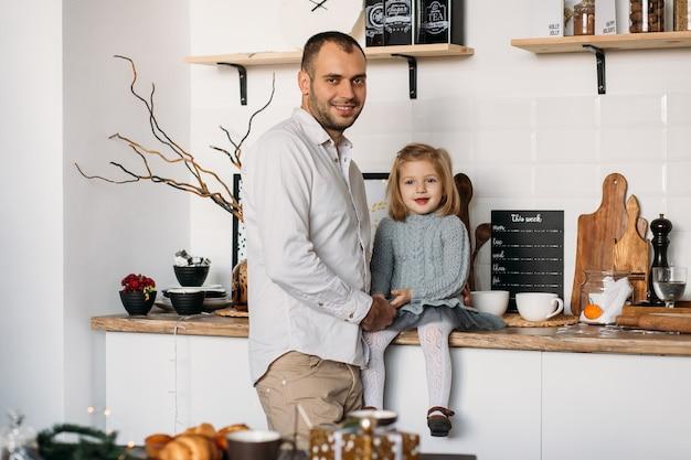 Vader en kleine dochter in keuken thuis. Premium Foto