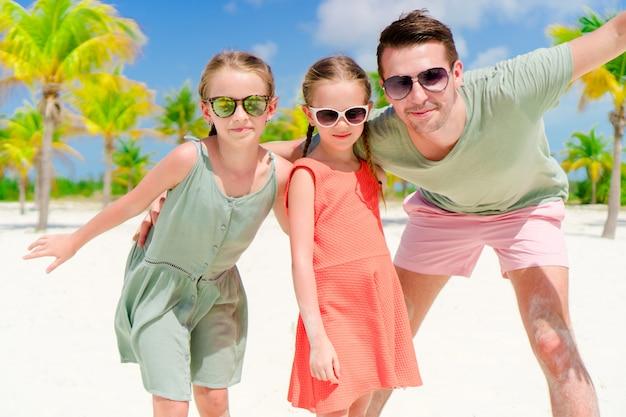 Vader en meisjes die pret op wit strand in palmbosje hebben Premium Foto