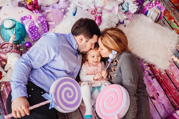 Vader en moeder houden grote roze snoepjes liggend met hun dochter op de grond Gratis Foto