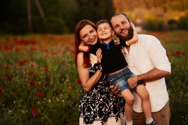 Vader en moeder houden hun zoontje op de armen staande op het groene veld met klaprozen Gratis Foto