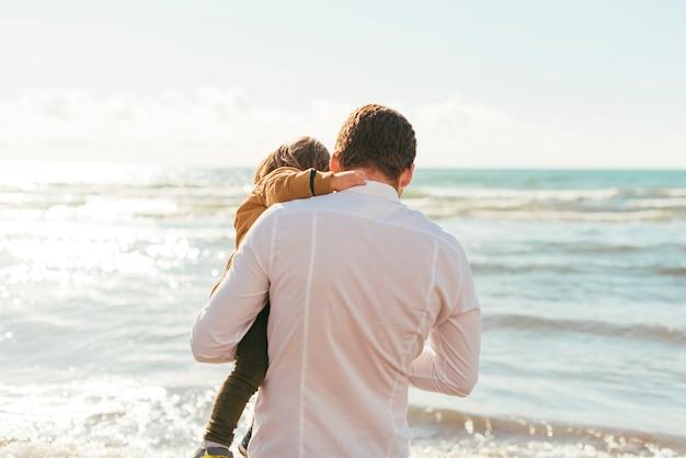 Vader en peuter die op zee golven kijken Gratis Foto