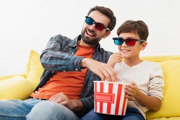 Vader en snel popcorn eten en een film kijken Gratis Foto
