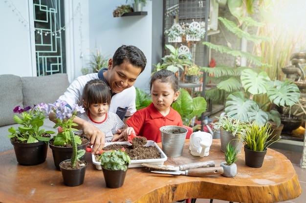 Vader en twee dochters zijn blij als ze een schep gebruiken om potplanten te kweken Premium Foto