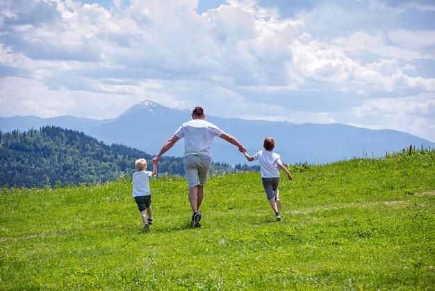 Vader en twee jonge zonen die op het groene veld hand in hand lopen Premium Foto