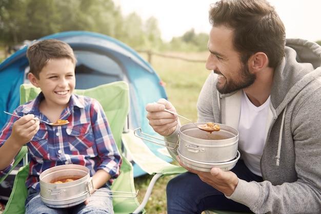 Vader en zijn zoon die diner op camping eten Gratis Foto