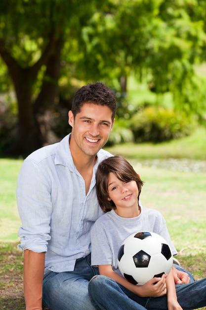 Vader en zijn zoon met hun bal in het park Premium Foto