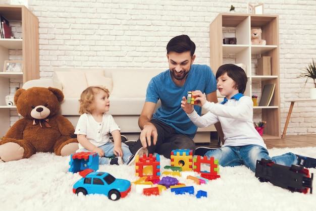 Vader en zonen spelen met speelgoed. Premium Foto