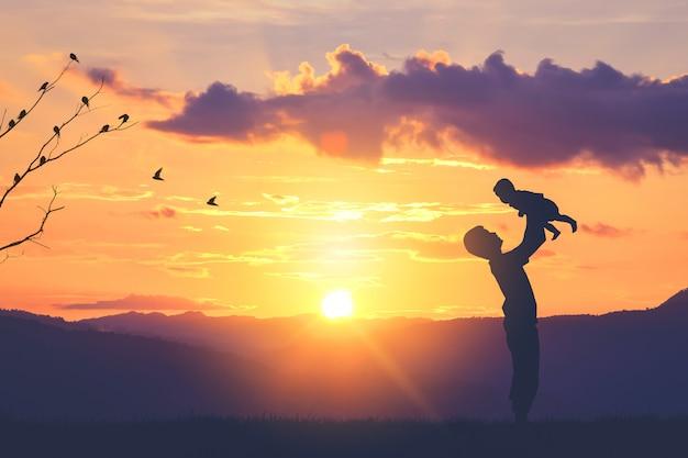Vader en zoon baby silhouetten spelen bij zonsondergang bergen Premium Foto
