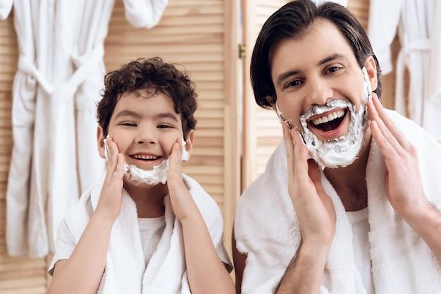 Vader en zoon bedekken het hele gezicht met scheerschuim. Premium Foto
