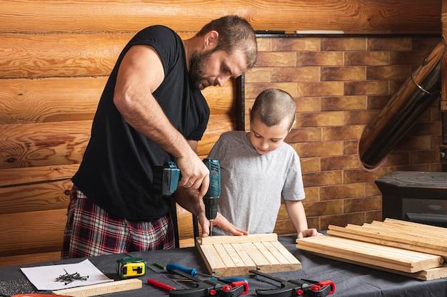 Vader en zoon boren een houten plank met een schroevendraaier, gereedschap en een balk op de tafel in de werkplaats Premium Foto