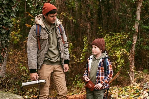 Vader en zoon buiten op een roadtrip in de natuur Gratis Foto