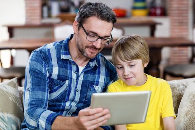 Vader en zoon die digitale tablet in keuken gebruiken Premium Foto