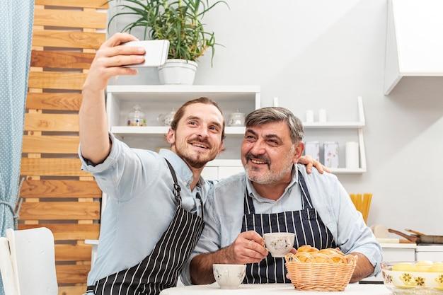 Vader en zoon die een selfie in keuken nemen Gratis Foto