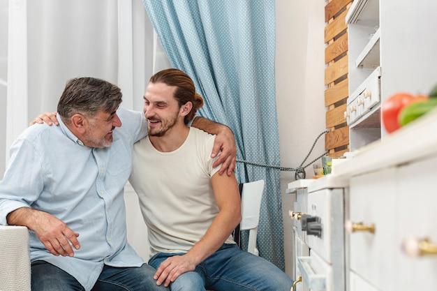 Vader en zoon die en in keuken omhelzen spreken Gratis Foto