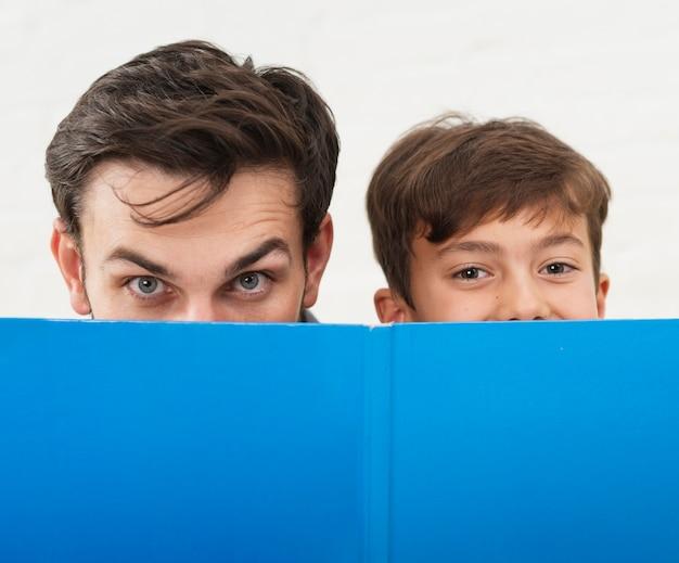 Vader en zoon die hun gezichten bedekken met een blauw boek Gratis Foto