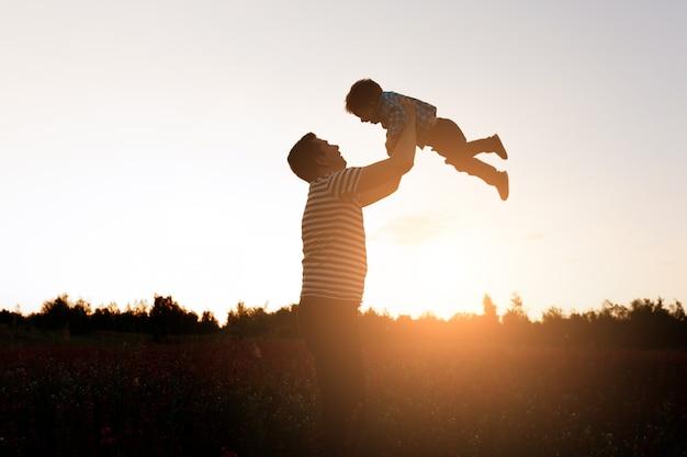 Vader en zoon die in het park in de zonsondergangtijd spelen. gelukkige familie plezier buiten Gratis Foto