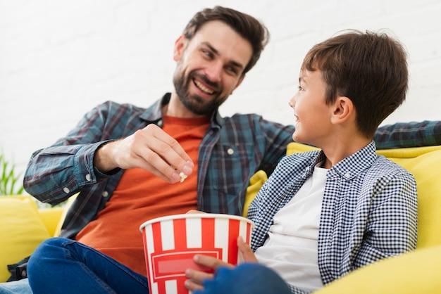 Vader en zoon die popcorn eten en elkaar bekijken Gratis Foto
