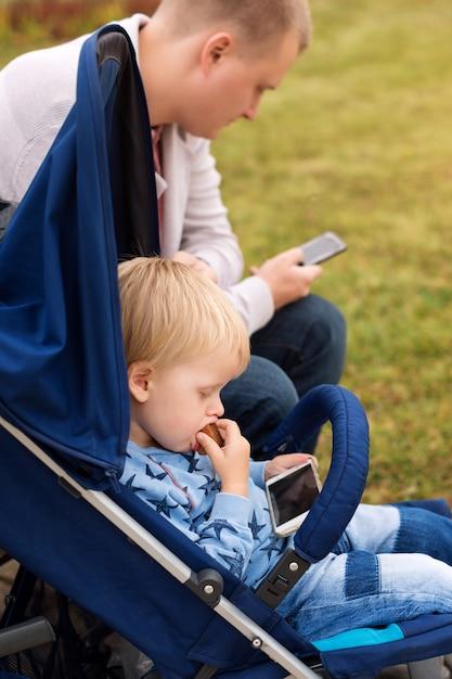 Vader en zoon die smartphones gebruiken terwijl samen tijd doorbrengen in de herfstpark. Premium Foto