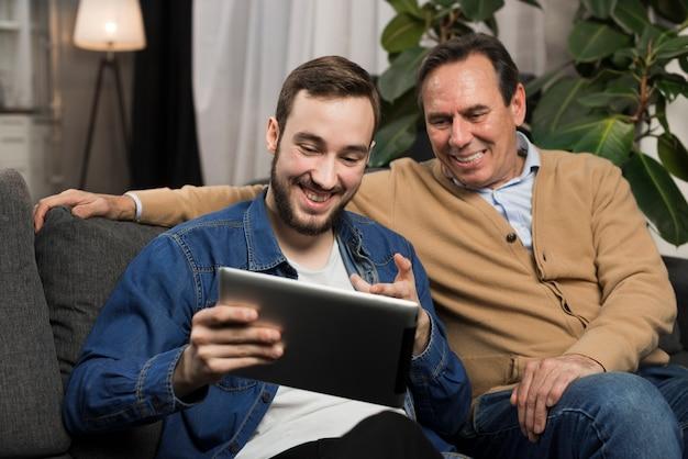 Vader en zoon die tablet in woonkamer bekijken Gratis Foto