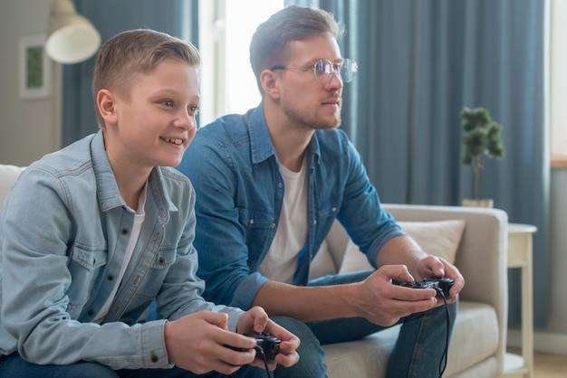 Vader en zoon die videospelletjes zijaanzicht spelen Gratis Foto
