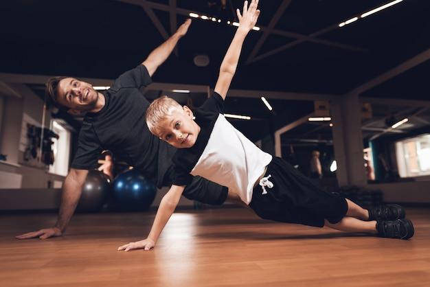 Vader en zoon doen persoefeningen in de sportschool. Premium Foto