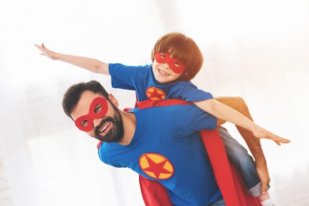 Vader en zoon dragen superhelden op gezichtsmaskers. Premium Foto
