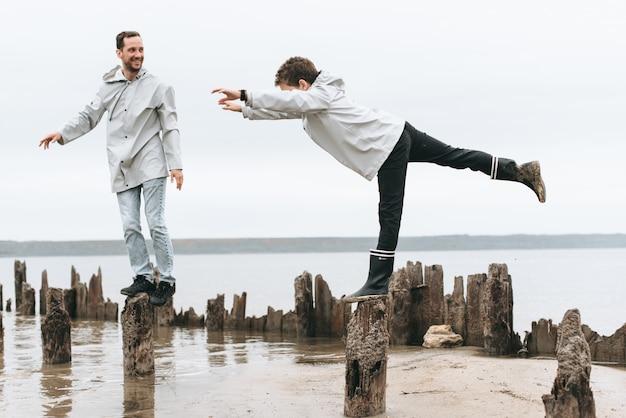 Vader en zoon hebben plezier en doen joga-oefeningen in een regenjas bij de zee Premium Foto