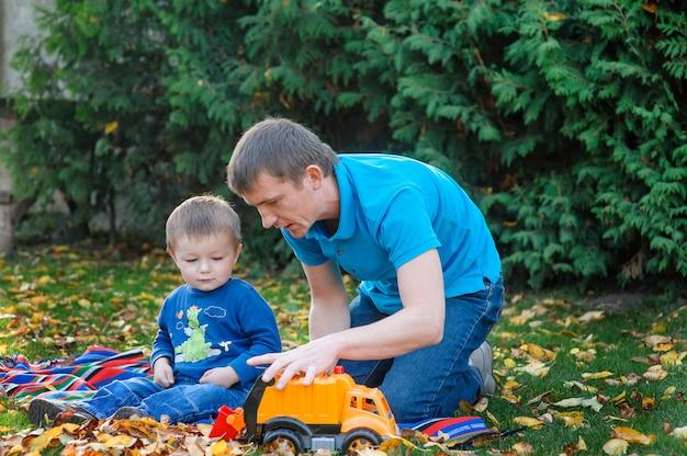 Vader en zoon het spelen in de parkstuk speelgoed auto in een park op het gras in de herfst Premium Foto