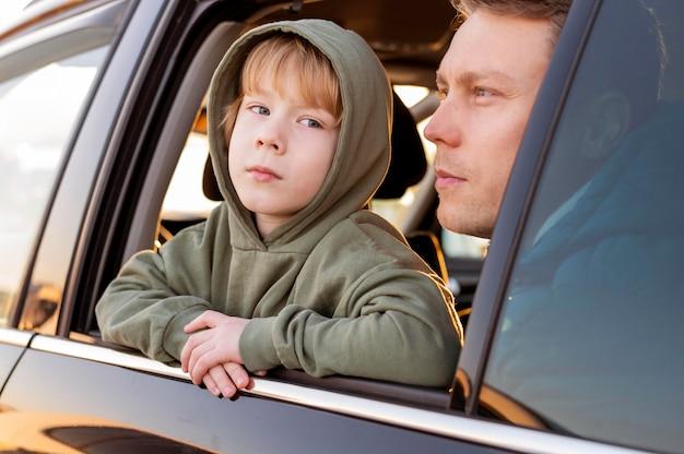 Vader en zoon in de auto die het uitzicht bewonderen tijdens een roadtrip Gratis Foto