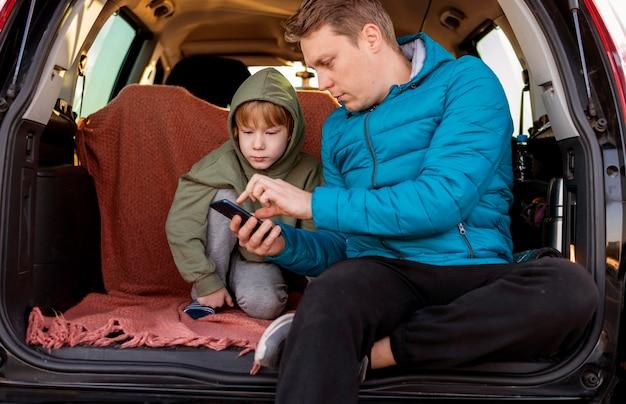 Vader en zoon in de auto met smartphone tijdens een roadtrip Gratis Foto