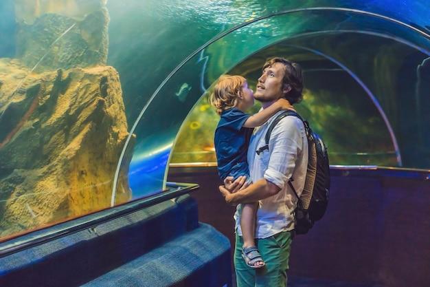 Vader en zoon kijken naar de vissen in het aquarium in oceanarium. Premium Foto