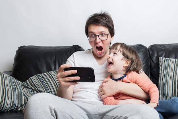Vader en zoon kijken naar een enge video op de telefoon. Premium Foto