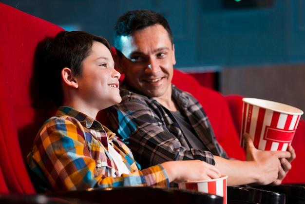 Vader en zoon kijken naar film in de bioscoop Gratis Foto