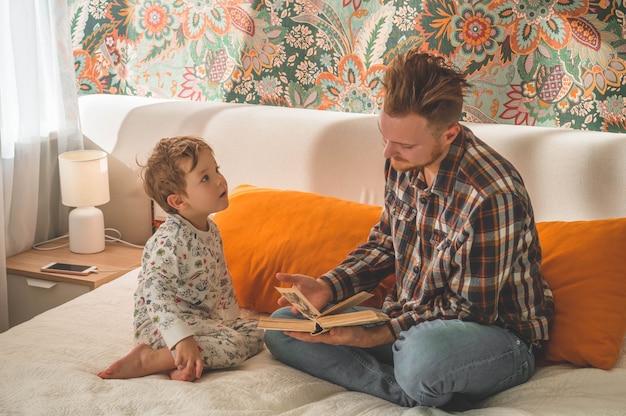 Vader en zoon lazen samen een boek, glimlachend en knuffelend. gezinsvakantie en saamhorigheid Premium Foto