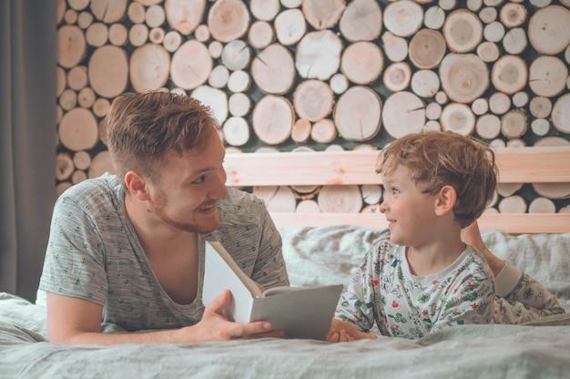 Vader en zoon lazen samen een boek, glimlachend en knuffelend Premium Foto