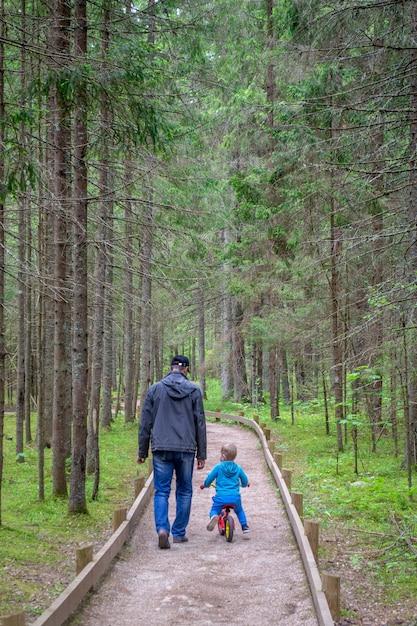Vader en zoon lopen in het bos. de mens met babyjongen gaat op weg. Premium Foto