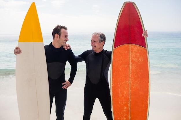 Vader en zoon met surfplank die zich op strand bevinden Premium Foto