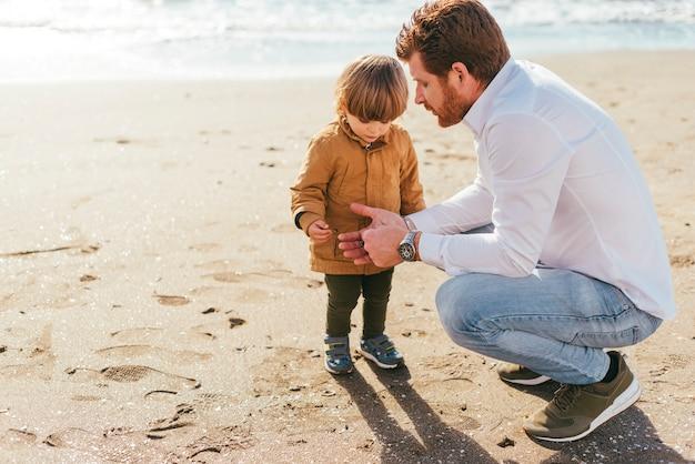 Vader en zoon op het strand Gratis Foto