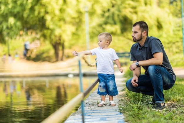 Vader en zoon plezier in de buurt van meer in zomer park Premium Foto