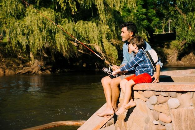 Vader en zoon samen buitenshuis Gratis Foto