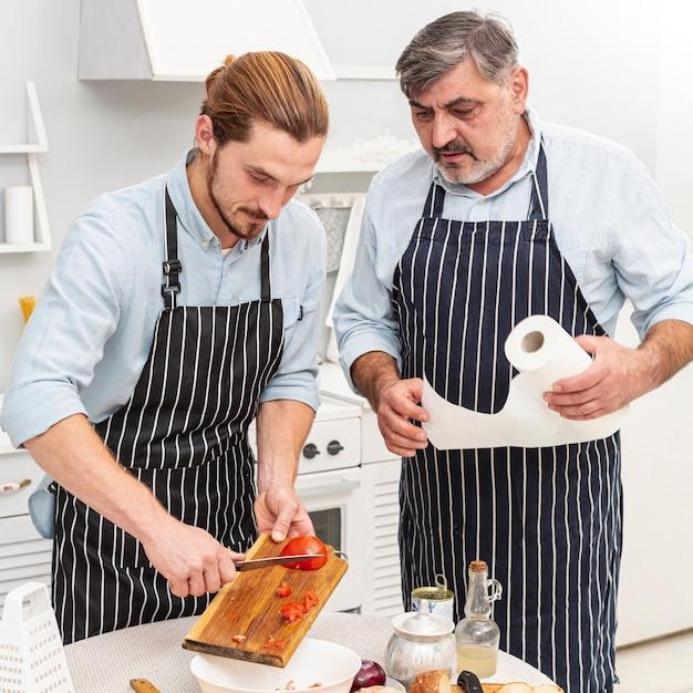 Vader en zoon scherpe tomaten Gratis Foto