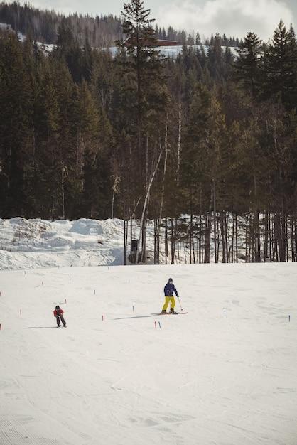 Vader en zoon skiën op besneeuwde alpen Gratis Foto