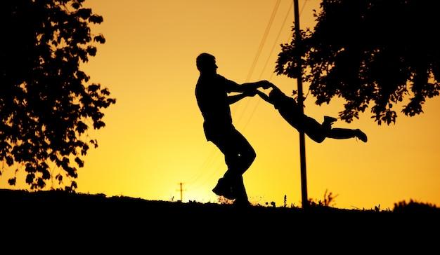 Vader en zoon spelen bij zonsondergang Premium Foto