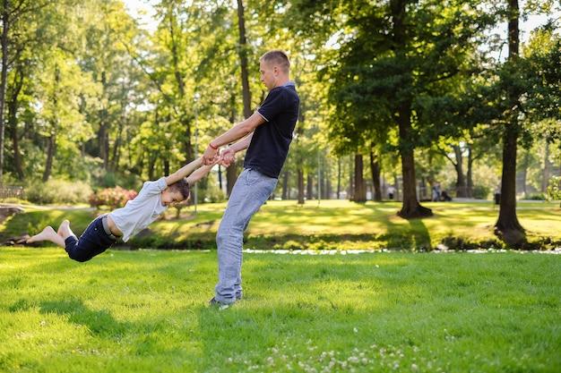Vader en zoon spelen in het park Gratis Foto