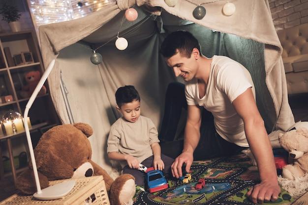 Vader en zoon spelen met auto's op de tapijtweg Premium Foto