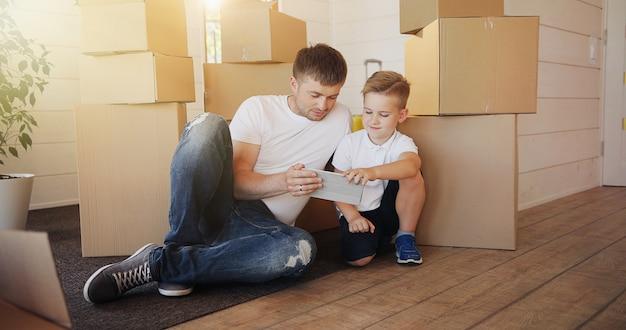 Vader en zoon spelen met digitale tablet omringd door dozen Premium Foto