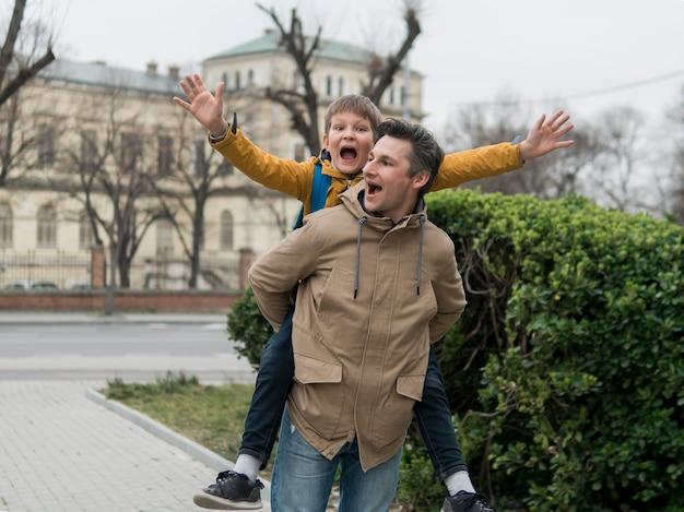 Vader en zoon spelen naast een park Gratis Foto