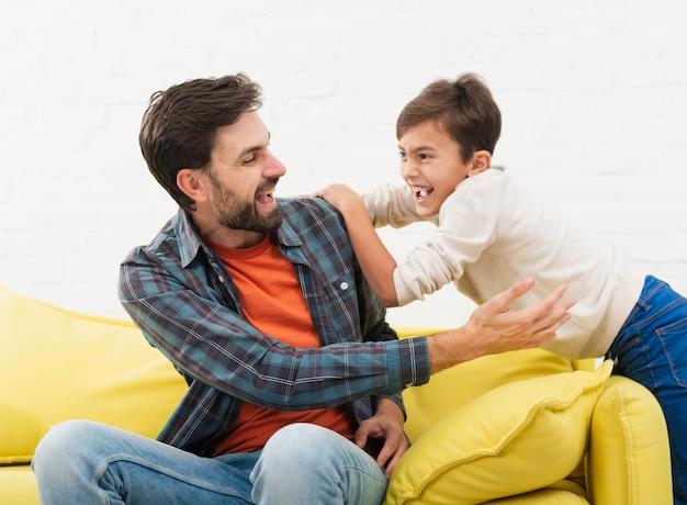 Vader en zoon spelen op de sofa Gratis Foto