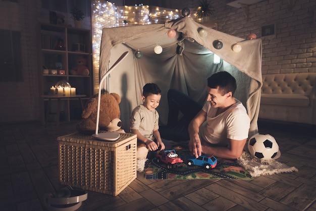 Vader en zoon spelen 's nachts thuis met speelgoedauto's. Premium Foto