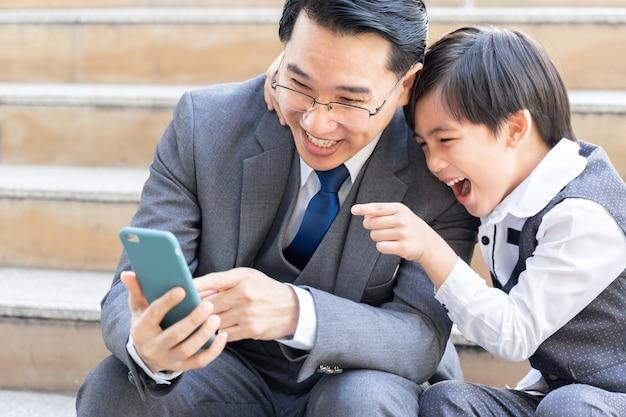 Vader en zoon spelen slimme telefoon samen op zakenwijk stedelijk Gratis Foto